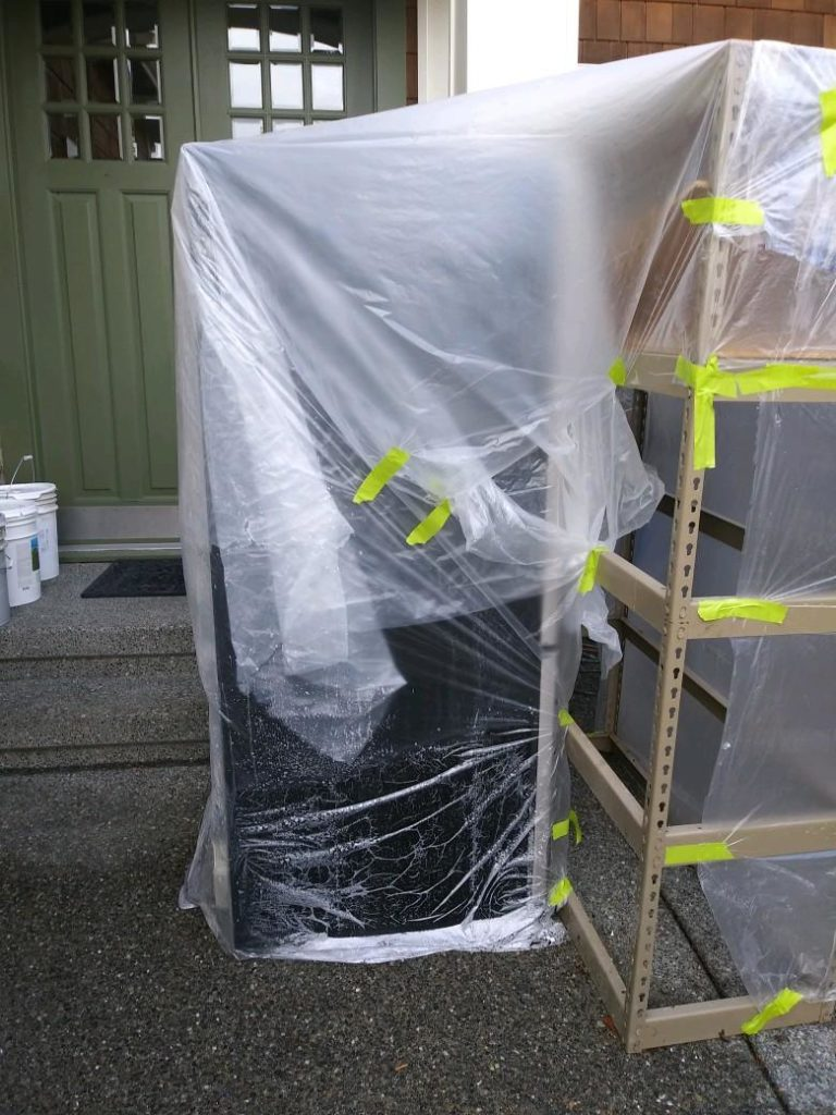 Appliances outside and tarped against the weather